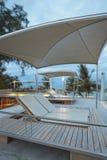 Deckchairs en la piscina fotografía de archivo