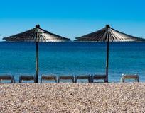 Deckchairs et parapluies de plage sur une plage Photos libres de droits
