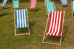 Deckchairs on a grassy lawn in the summer. stock photos