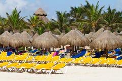 Deckchairs met parasols bij Caraïbische Zee Stock Foto's