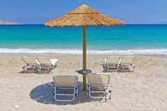 Deckchairs onder parasol bij Egeïsche Overzees Stock Afbeelding