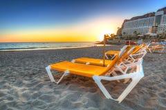 Deckchairs op het strand van Taurito bij zonsondergang Stock Foto