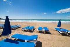 Deckchairs på den Benidorm stranden Arkivfoto
