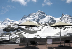 Deckchairs and parasols with view of Breithorn Royalty Free Stock Image