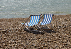 Deckchairs on pebble beach Stock Images