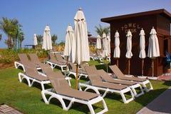 Deckchairs perto da mesa de toalha Imagem de Stock Royalty Free