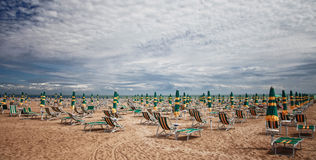 Deckchairs on sandy beach Royalty Free Stock Images