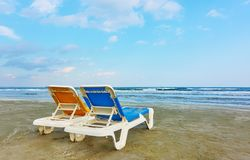 Deckchairs on a sandy beach. Vacant deckchairs on a sandy beach by the sea in the evening royalty free stock images