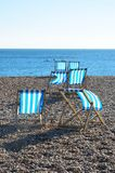 Deckchairs on shingle beach. In brighton Stock Photography