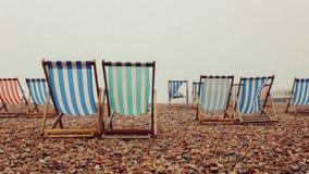 Deckchairs som är tom i Brighton, UK arkivbild
