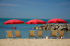 Deckchairs with sunshades on the beach. In italy stock photo