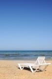 Deckchairs sur la plage sous le ciel bleu Images libres de droits