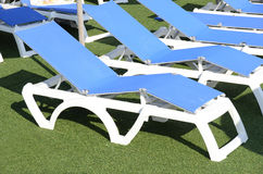 Deckchairs beside the swimming pool Royalty Free Stock Images