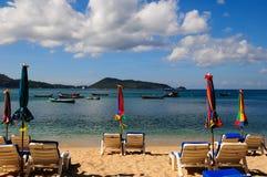 Deckchairs on the white sand beach facing the sea Stock Photos