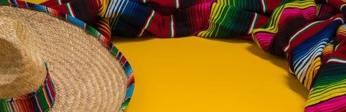 Decke des Mexikaners Sobrero und Serape auf gelbem Hintergrund mit Spindel Stockbilder