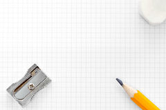 Decken Sie quadrierten Zeichenpapier mit Maßeinteilungradiergummi und -bleistiftspitzer ab Stockfoto