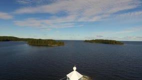 Decken Sie Schuss von See Vaner, Schweden auf und hinter historischem hölzernem Leuchtturm auftauchen stock video footage