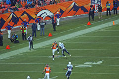 Decker takes a cheap shot. Eric Decker takes a cheap shot after the ball passes both players. (note the football behind decker before impact stock images