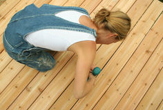 Decking. A new home owner builds her own deck to save money stock photo