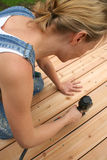 Decking. A girl uses an air gun to nail her new deck royalty free stock photo