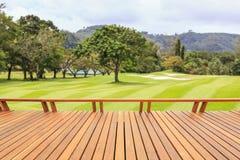 Decking del legno duro o pavimentazione e vista del campo verde in cou di golf immagini stock libere da diritti
