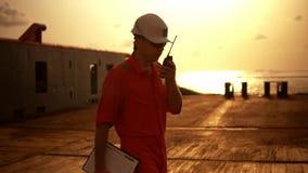 Deckoffizier auf Plattform des Offshoreschiffes h?lt VHF-Funksprechger?tradio stock footage