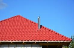 Deckungs-Bau Neues rotes Metall deckte Dach mit dem Stahlkaminhaus-Deckungsbau mit ziegeln, der ohne Regengossensystem außen ist lizenzfreies stockbild
