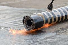 Deckungsinstallationsfilz mit Heizung und schmelzende Bitumenrolle durch Fackel auf Flamme, Nahaufnahmedetailtrieb stockfotos