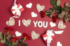 Declaração do amor com presentes, as flores cor-de-rosa e corações decorativos no fundo vermelho foto de stock royalty free