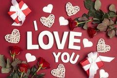 Declaração do amor com presentes, as flores cor-de-rosa e corações decorativos no fundo vermelho Conceito do dia de Valentim do S imagem de stock royalty free