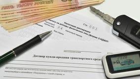 Declaración de impuestos y contracto de venta del coche Las llaves al coche y a cinco mil notas Imágenes de archivo libres de regalías