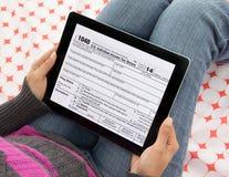 Declaraciones sobre la renta de la limadura de la persona en línea usando la tableta Foto de archivo