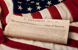 Declaration of Independence on an American flag. Close-up of the Declaration of Independence rolled up on an American flag Royalty Free Stock Photography