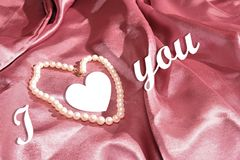 Declaration of love. White pearls on a pink satin background Royalty Free Stock Photos