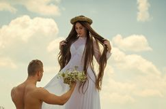 Declaration of love. Macho with muscular torso give flowers to woman Stock Images