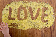 Declaration of love painted millet. Child draws on a table with crumbles millet. Royalty Free Stock Images