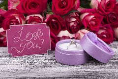Declaration of love with a ring. Gift in the box and the inscription. Ring with stone and flowers stock photos