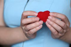 Declaration of love, woman holding red knitted heart on her chest royalty free stock photography