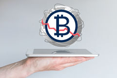 Decline of global bitcoin currency exchange rate concept with hand holding tablet.  royalty free stock images