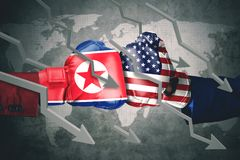 Declining arrows with two boxing gloves. Concept of conflict. Two boxing gloves with North Korea and USA flag, declining arrows Stock Photography