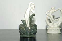 Deco flower frogs. Standing nude lady woman ceramic figurine colored white and green symmetrical and geometric shaped retro Art deco flower frog female statue royalty free stock photography