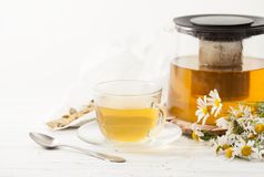 A decoction of chamomile flowers in a tea Cup on the table Royalty Free Stock Photos