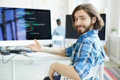 Decoding specialist. Young successful specialist in data decoding sitting by workplace and pointing at computer monitor royalty free stock photo