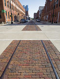Decommissioned railroad tracks and industrial buildings. Dubuque, Iowa, October 2016: Decommissioned train tracks run down the street of the historic Millwork Stock Images