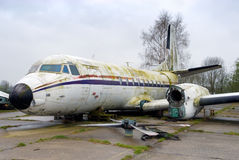 Decommissioned vintage airplane. Decommissioned but intact vintage airplane with detached wings and propeller engines, and covered with moss and alga laying on a royalty free stock photo