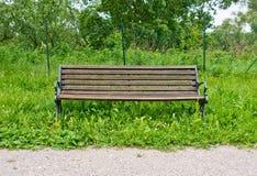 Decomponga, banco isolato nel parco in mezzo ad erba alta Immagini Stock
