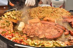 Decomposed street food on a large metal tray, close up.Fried chicken,sausages, fried zucchini,meat,fish,Uzbek pilaf. Decomposed street food on a large metal tray royalty free stock images