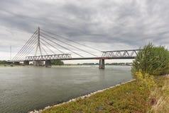 Deconstruction av en gammal bro bredvid en ny upphängningbro arkivfoto