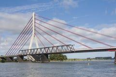 Deconstruction av en gammal bro bredvid en ny upphängningbro royaltyfria bilder