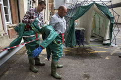 Decontamination tent and men removing their protective clothing Royalty Free Stock Images